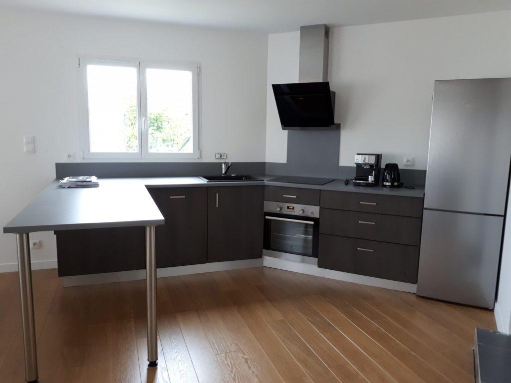 Création d'une cuisine décor bois sombre et stratifiée gris anthracite. Intégration de l'électroménager fourni par le client.